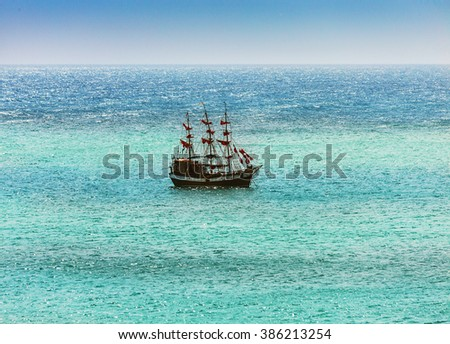 Old ship with sails, sailing in the sea - stock photo