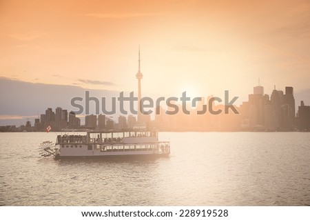 Old ship with young people on the rest at sunset time. Ontario lake. Canada. Vintage image. - stock photo