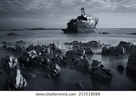 Old shipwreck long exposure on the rocks at sunset artistic conversion