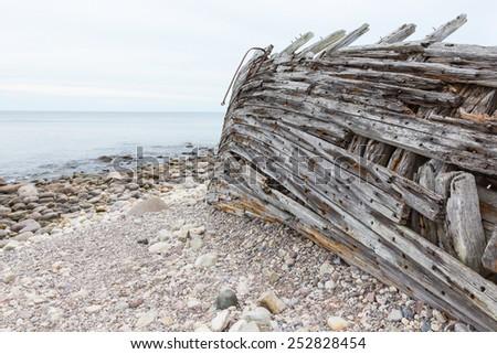 Old shipwreck on a sea shore - stock photo