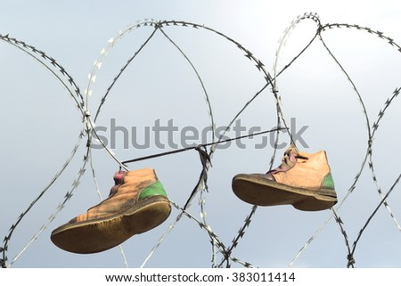 Old shoes hanging on the razor wire - stock photo