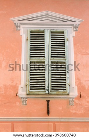 Old shutters with a faux painted window frame in a pink wall - Montalcino, Tuscany, Italy - stock photo