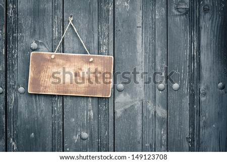 Old sign board blank hanging on vintage black wood planks background - stock photo