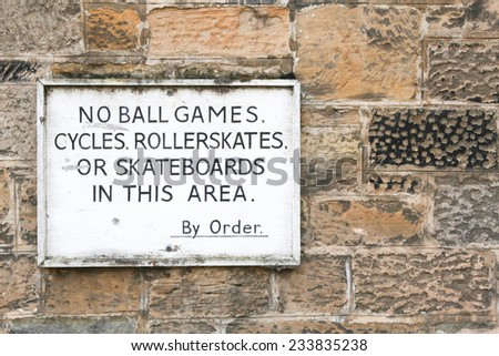 Old sign prohibiting ball games, cycling, roller skates and skateboarding on a stone wall background - stock photo