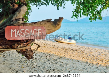 Old signboard with the inscription, massage, on a tropical beach - stock photo