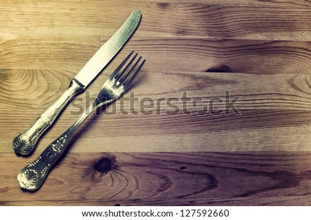 Old silver cutlery on wooden background, vintage image - stock photo