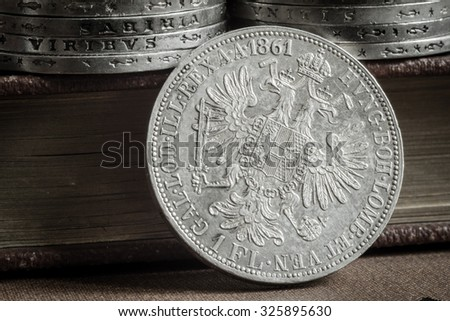 Old silver forint coins with old books. - stock photo