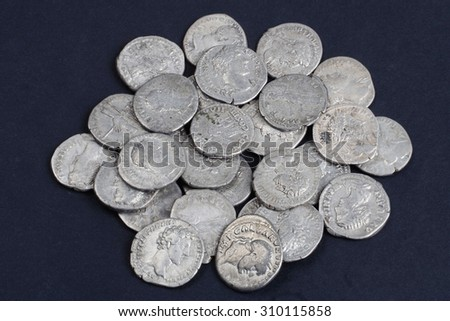 old silver roman coins on a black background - stock photo