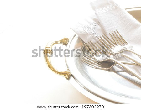 Old silver tray with napkin and forks - stock photo