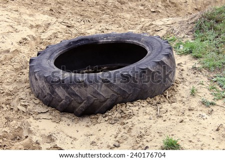 old single black tire lying on the sand - stock photo