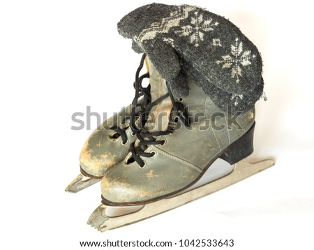 old skates and knitted mittens on a white background