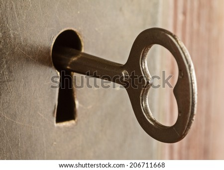 Old skeleton key in keyhole lock  - stock photo
