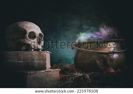 old skull on old book and copper cauldron on textured background