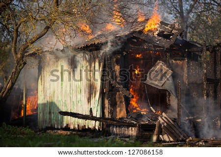 Old small building in full flaming - stock photo