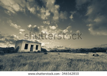Old small deserted house in field with a cloud sunset landscape artistic conversion - stock photo