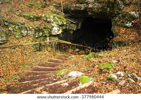 Old small mine entrance, with steps leading downwards. - stock photo