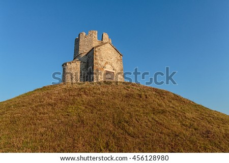 Old small stone church of St. Nicholas on hill near city of  Nin in Croatia. Golden hour