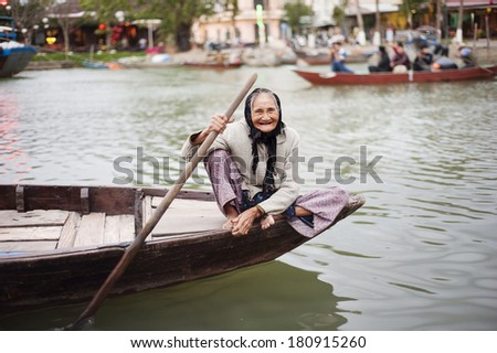 Old smiling elderly woman sailing canoe on the river in Vietnam. - stock photo