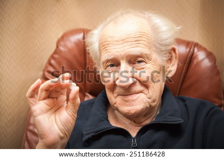 old smiling man holding a tablet, he is going to take some medicine - stock photo