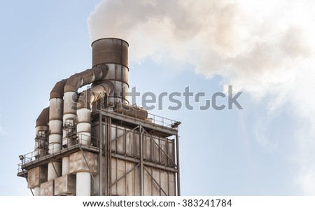 Old smokestack that emits white smoke in the clear blue sky. - stock photo