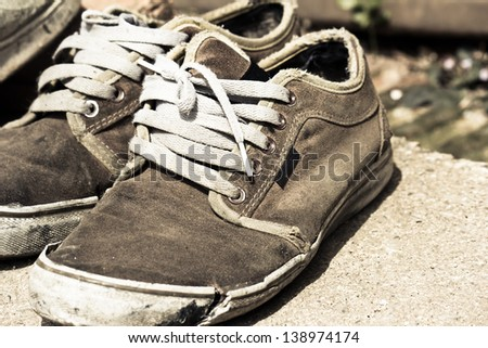 old sneaker  on grungy background - stock photo