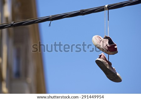 Old sneakers hanging from a cable. - stock photo