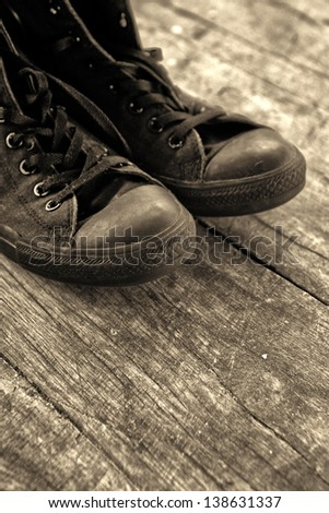 Old sneakers. Old black sneakers on wooden floor, monochromatic image.