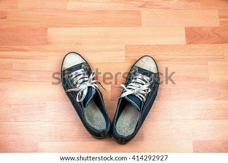 Old Sneakers on Wooden Floor.