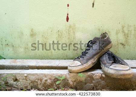 Old sneakers placed in front of a green wall,selective focus point.