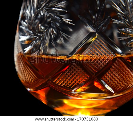 old snifter with brandy , isolated in black , saved clipping path - stock photo
