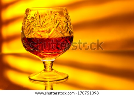 old snifter with brandy on mirror table - stock photo