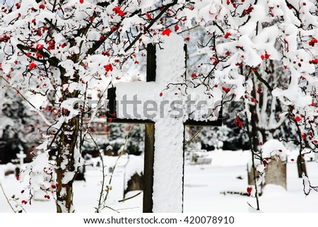 Old snow covered granite stone cross found in an old graveyard in winter, - stock photo