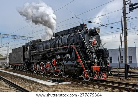 Old soviet steam locomotive series L arriving at railway station. - stock photo