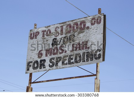 Old speeding sign on side of road. - stock photo