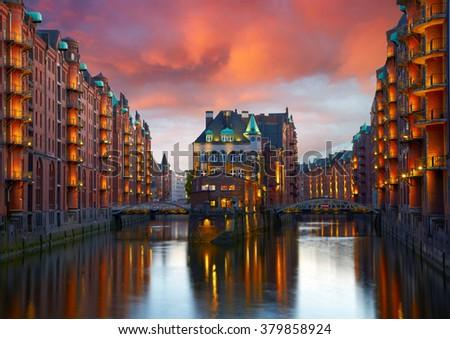 Old Speicherstadt in Hamburg illuminated at night. Sunset background - stock photo