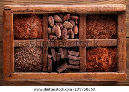 old spicy box full of chocolate - cocoa and sugar, cocoa beans, grated chocolate, hot chocolate flakes, solid pieces, dark cocoa powder - stock photo