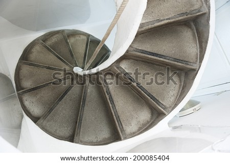 Old Spiral Staircase with rope handrail - stock photo