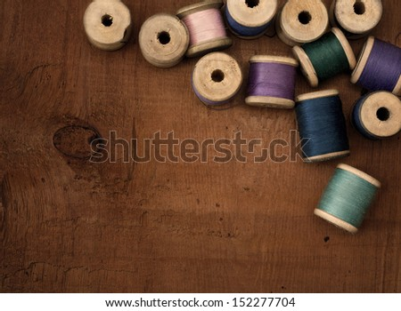 Old spools of thread on a wooden background - stock photo