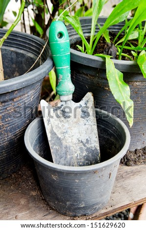 Old spoon to dig a planting plowing and plastic vase .  - stock photo