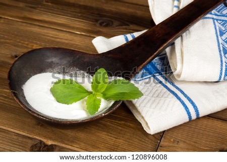 Old spoon with natural sweetener stevia and a fresh stevia leaf - stock photo