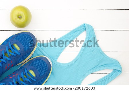 Old sport shoes, shirt and apple on a white wooden background. Sport equipment top view