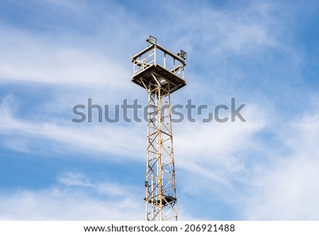 Old spotlight tower under the clear blue sky. - stock photo