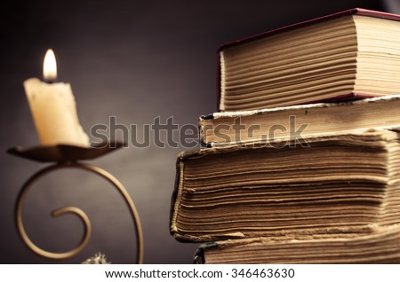 Old stacked book and candle  horizontal photo - stock photo