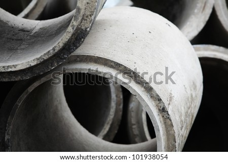 Old stacked concrete drainage pipes - stock photo