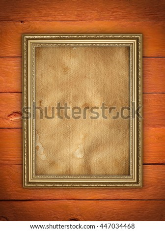 Old stained paper sheet in picture frame on wooden background