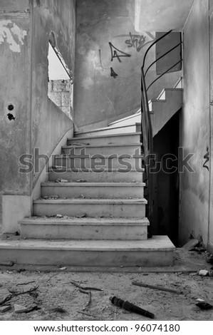 Old staircase and dirty floor in abandoned building interior. Black and white. - stock photo