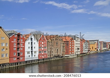 Old stately warehouses in Trondheim line the banks of the river