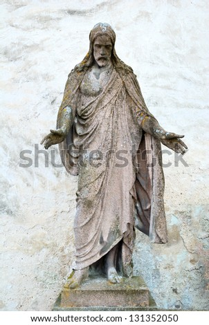 Old statue of Jesus Christ with a grungy wall behind - stock photo