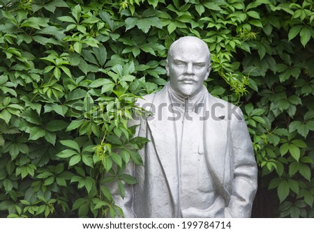 Old statue of Lenin looks out from the bushes - stock photo