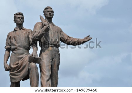 Old statue of two labour from epoch of socialism.